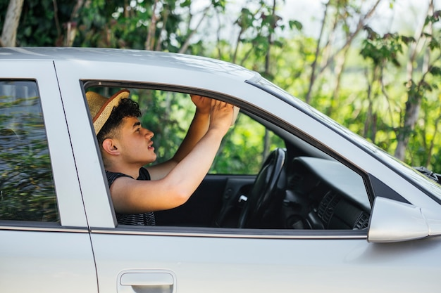 Side view of man adjusting car mirror while sitting in car