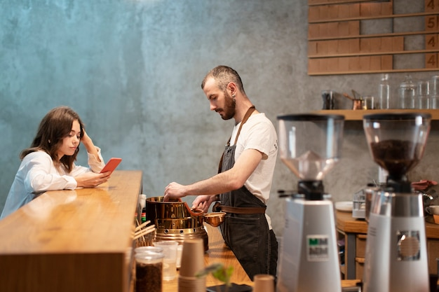 Side view of man in apron with customer