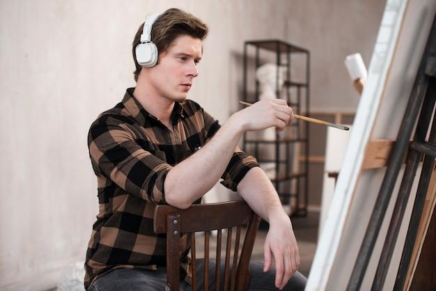 Вид сбоку мужчина художник рисует на холсте