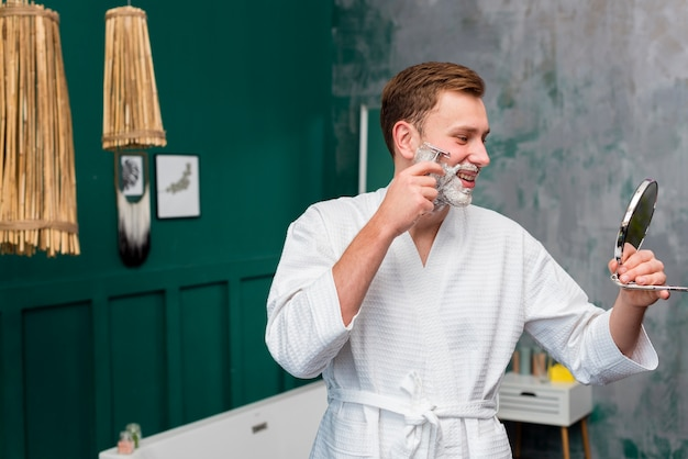 Side view of man in bathrobe shaving
