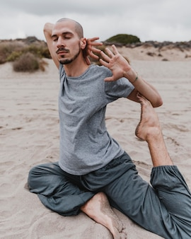 Side view of man on the beach exercising yoga