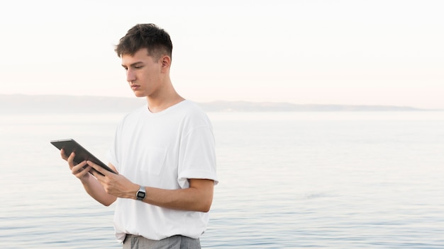 Side view of man at the beach holding tablet with copy space