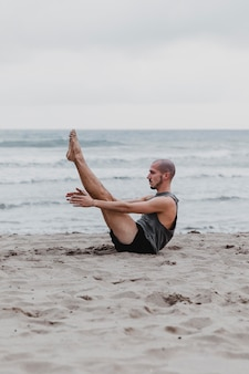 Side view of man on the beach in yoga position with copy space