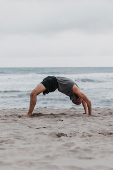 Side view of man on the beach in yoga position
