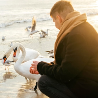 Side view of man by the beach in winter with birds
