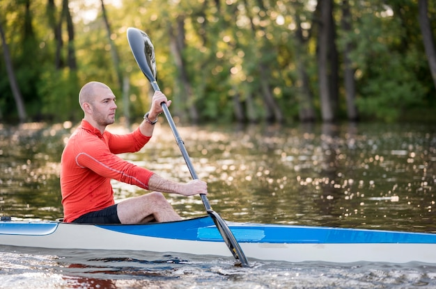 Side view man in canoe with paddle