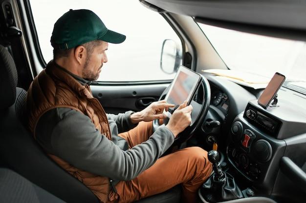 Uomo di vista laterale in macchina che consegna il pacchetto