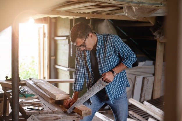 Side view of a man carpenter with glasses sawing a wooden board in the home workshop