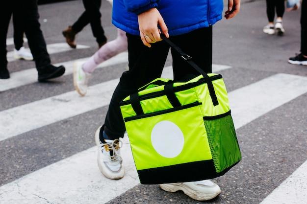 サイドビューの男性が歩行者ゼブラ道のライトグリーンのバッグで注文を運ぶ