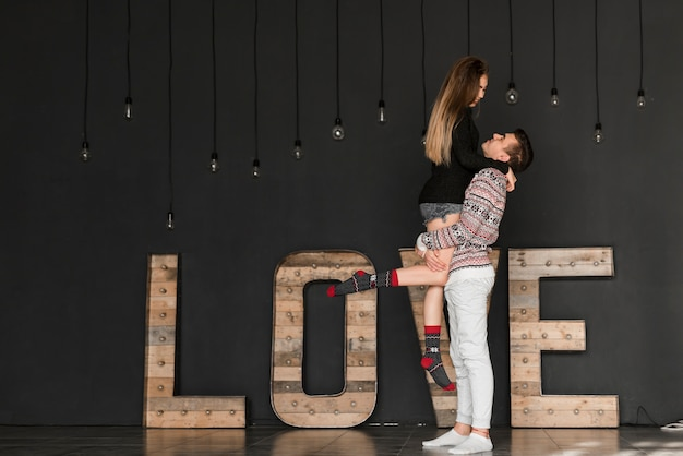 Side view of a man carrying her girlfriend standing in front of wooden love text against black background