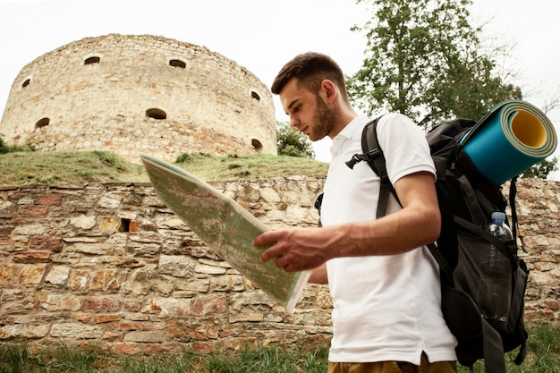 Side view man at castle ruins with map