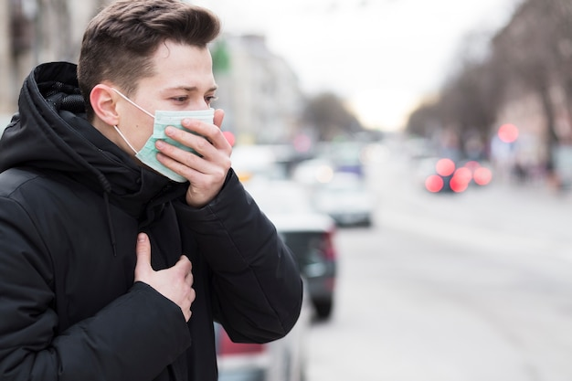 Side view of man in city coughing while wearing a medical mask