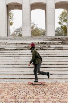 Vista laterale dell'uomo in città in sella al suo skateboard