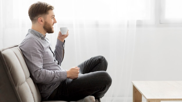 Side view man on couch drinking coffee