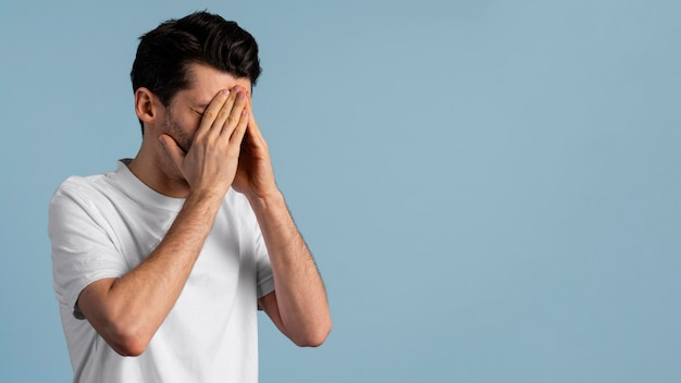 Side view of man covering his eyes with his hands