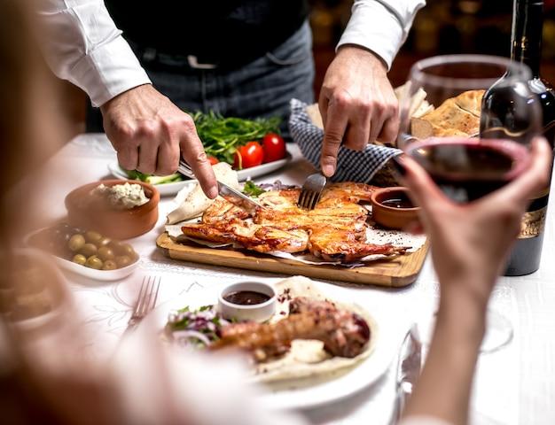 Vista laterale un uomo taglia il tabacco sul pane pita con salsa e cipolle con verdure e pomodori