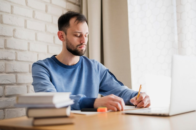 Side view of man at desk being online tutored