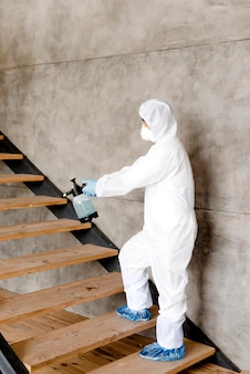 Side view man disinfecting stairs