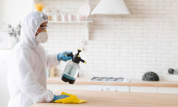 Side view man disinfecting table