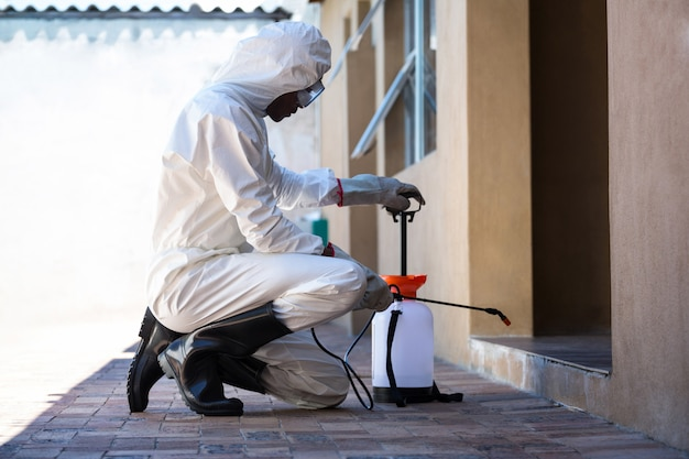 Side view of a man doing pest control