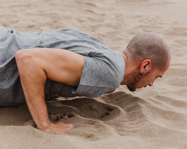 Side view of man doing yoga on sand