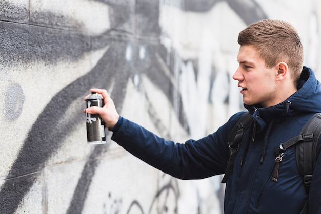 Side view of a man drawing graffiti with spray