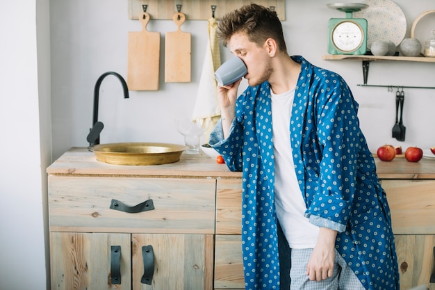 Side view of man drinking coffee standing near sink at home