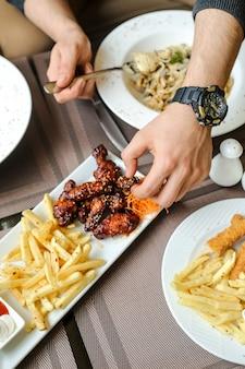 Боковой вид человек ест барбекю куриные крылышки с картофелем фри и салатом на столе