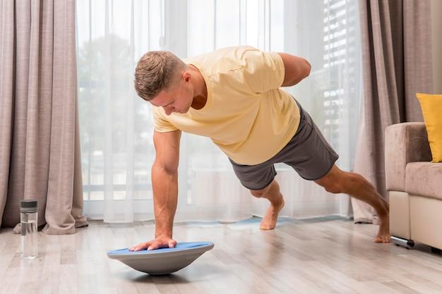 Вид сбоку человек, тренирующийся дома с мячом босу