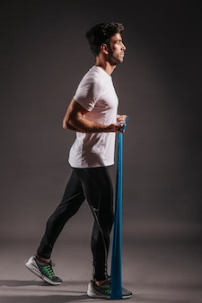 Side view man exercising with elastic band