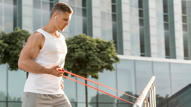 Side view man exercising with a red stretching band
