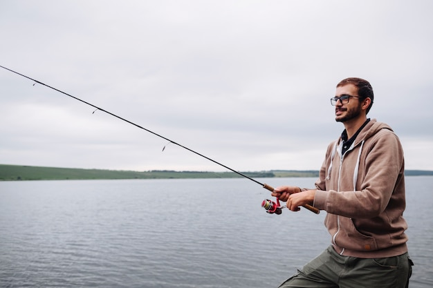 Side view of man fishing with rod on lake