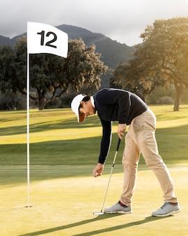 Vista laterale dell'uomo accanto alla bandiera sul campo da golf