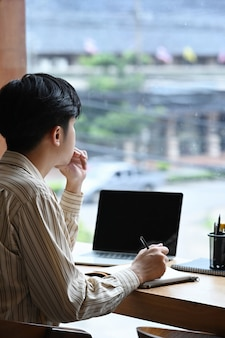 Side view man freelancer sitting near window and working with laptop computer.