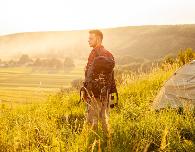 Side view man in green field with backpack