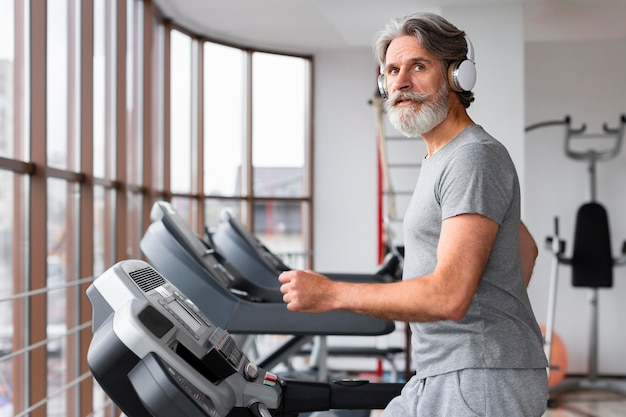 Side view man at gym on treadmill