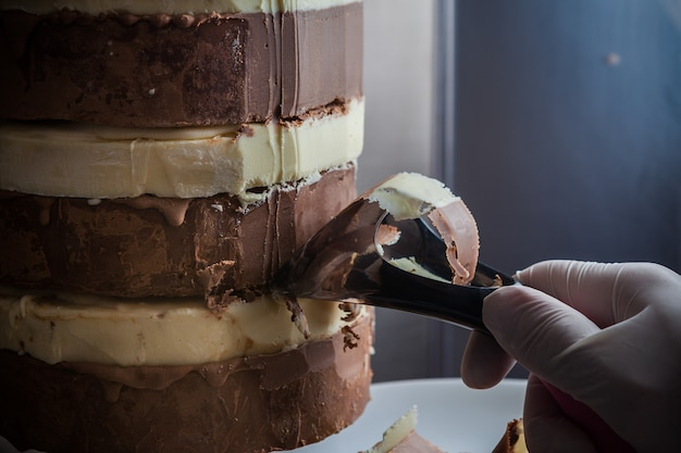 Side view man hand slicing black and white chocolate in plate