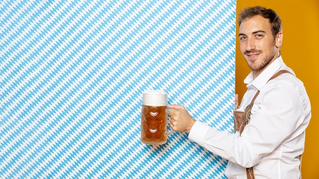 Side view of man holding beer pint