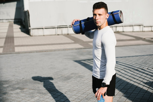 Side view of man holding fitness mat