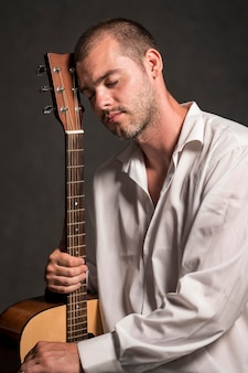 Side view man holding his head on guitar headstock
