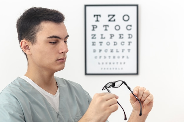 Side view of man holding and looking at pair of glasses