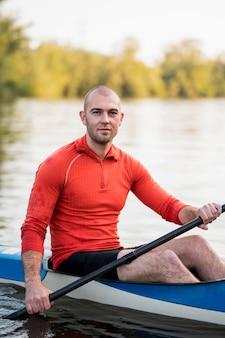 Side view man holding oar