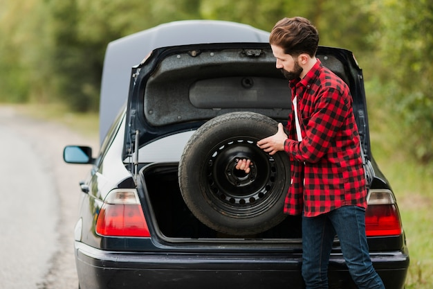 Side view of man holding spare tire