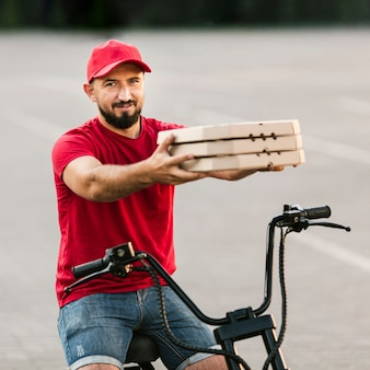 Side view man holding up pizza boxes
