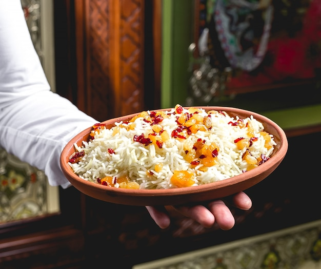 Side view a man holds a plate with boiled rice with raisins and barberries