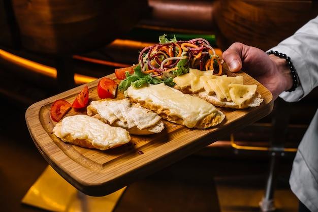 Vista laterale un uomo tiene un vassoio con toast di formaggio con fette di pomodoro e insalata di verdure