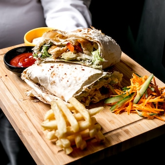 Side view a man holds a tray with chicken doner in pita bread with ketchup mayonnaise french fries and vegetable salad on the board