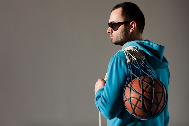 Side view of man in hoodie holding basketball in net with copy space
