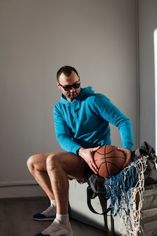 Side view of man in hoodie holding basketball