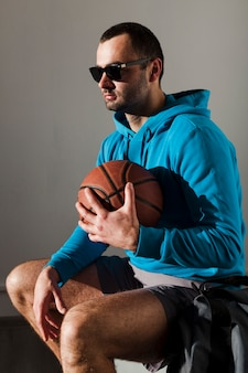 Side view of man in hoodie and sunglasses holding basketball close to chest